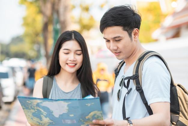 Traveler asian couple direction on location map in bangkok, thailand Free Photo