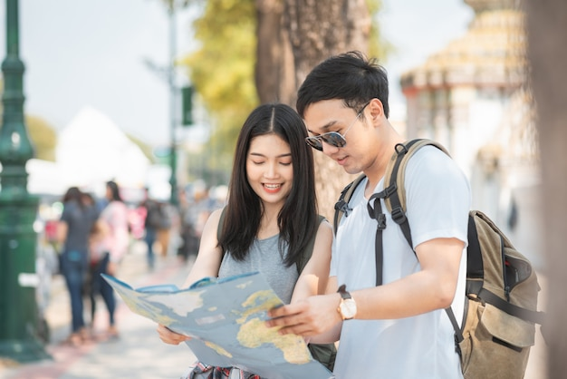Traveler asian couple direction on location map in bangkok, thailand Free Photo