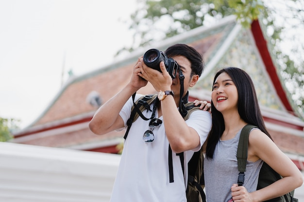 Traveler asian couple using camera for take a picture while spending holiday trip at bangkok, thailand Free Photo