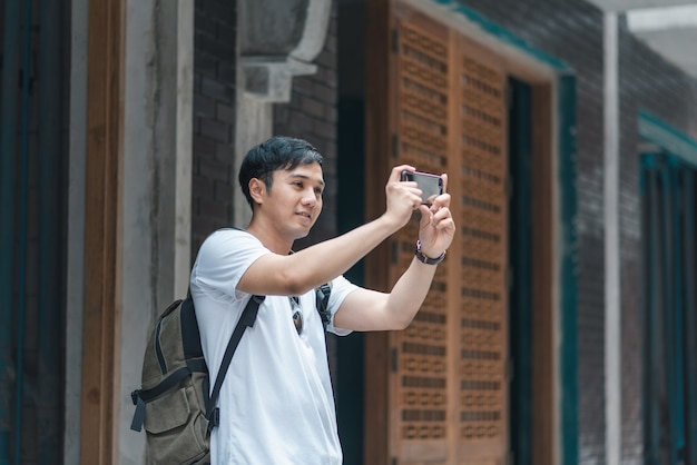 Traveler asian man using mobile phone for take a picture while spending holiday trip at beijing, china Free Photo
