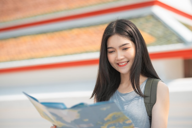 Traveler asian woman direction on location map in bangkok, thailand Free Photo