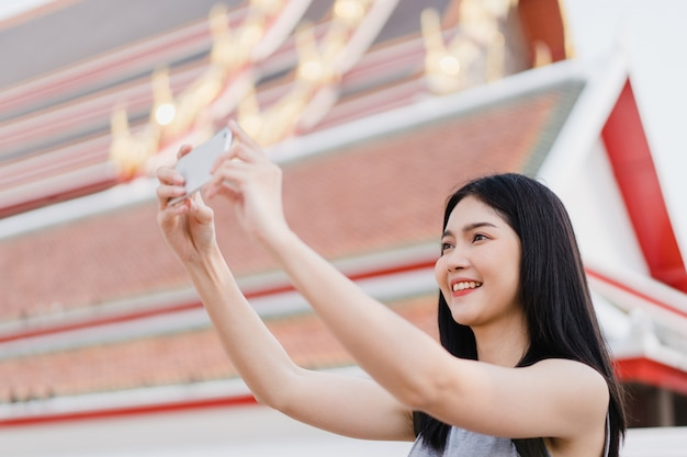 Traveler asian woman using mobile phone for take a picture while spending holiday trip at bangkok, thailand Free Photo