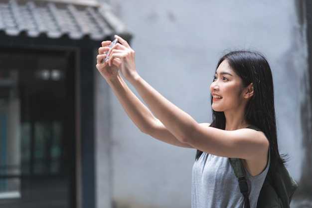 Traveler asian woman using mobile phone for take a picture while spending holiday trip at beijing, china Free Photo