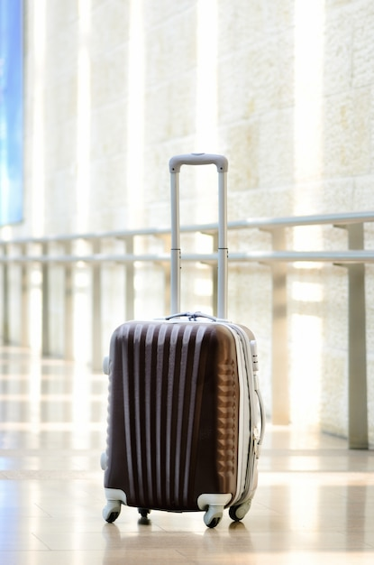 Traveler baggage, brown luggage in empty hall interior. copy space Premium Photo