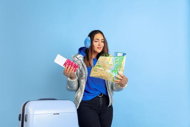 Viaggiatore. ritratto della donna caucasica su sfondo blu studio. bello modello femminile in vestiti caldi. concetto di emozioni umane, espressione facciale, vendite, annuncio. atmosfera invernale, periodo natalizio, vacanze. Foto Gratuite