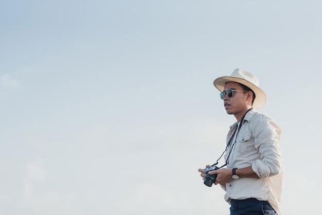 トラベラーコンセプト:白い空を背景に写真を撮るのを楽しみにして携帯電話にカメラを持っているアジア人男性。 Premium写真