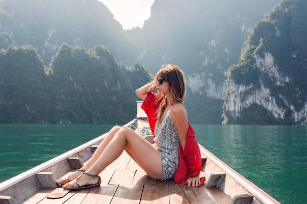 ボートでリラックスし、驚くほどの巨大な熱帯の崖を探索する旅行者の女の子。風の強い髪、歓喜、自由。タイ、アジア。 無料写真