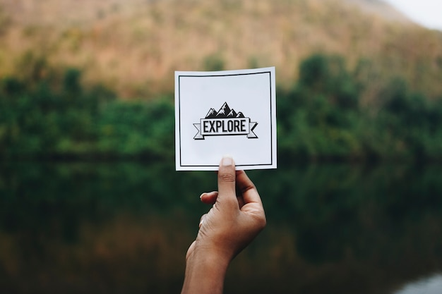 Traveler holding up a note in nature mockup Premium Photo