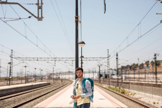 Traveler looking for train on station platform Free Photo