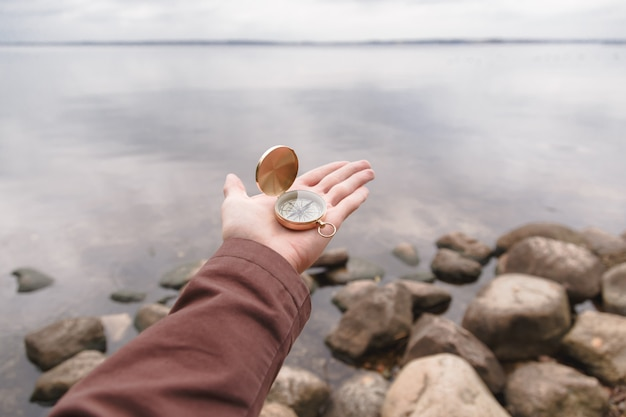 A traveler man holds a compass in his hand, standing on a stone beach. Premium Photo