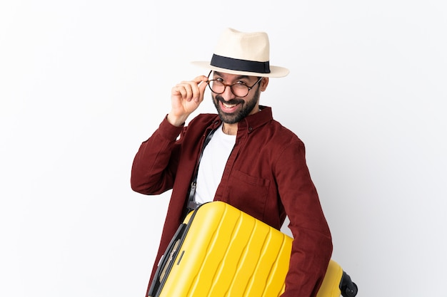 Traveler man man with beard holding a suitcase over white with glasses and smiling Premium Photo