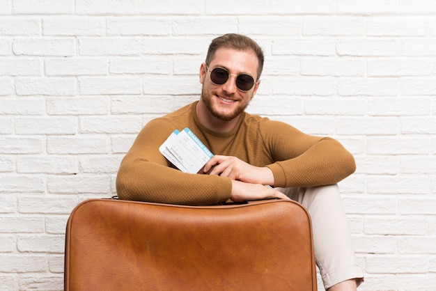 Traveler man with suitcase and boarding pass Premium Photo