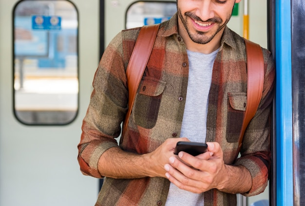 Traveler in metro using phone Free Photo