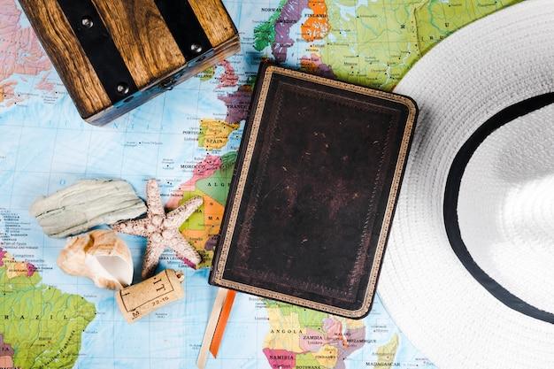 Diario del viaggiatore, conchiglia e cappello sulla mappa Foto Gratuite