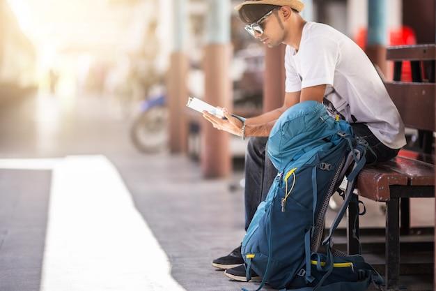 Путешественник сидя самостоятельно на деревянном стуле на вокзале. Premium Фотографии