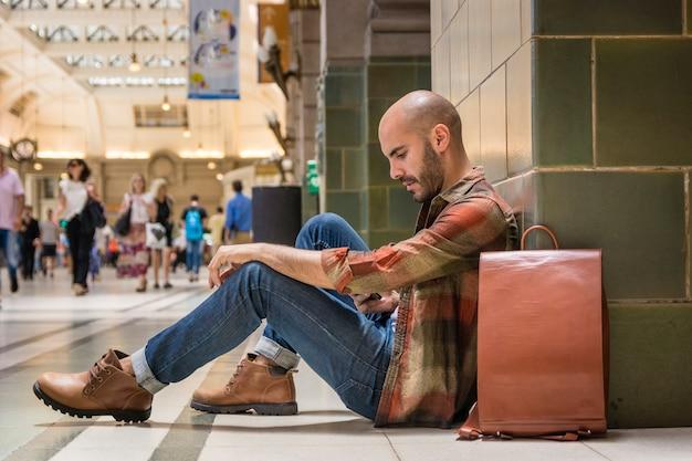 Traveler sitting on subway floor Free Photo