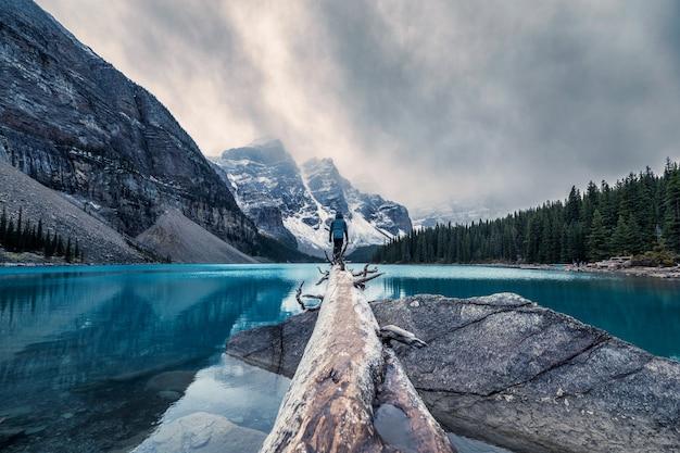 Traveler standing on log in maraine lake on gloomy day at banff national park Premium Photo
