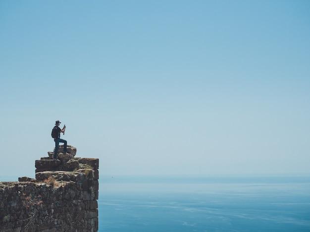 スマートフォンで素晴らしい海の景色の写真を撮る旅行者 Premium写真