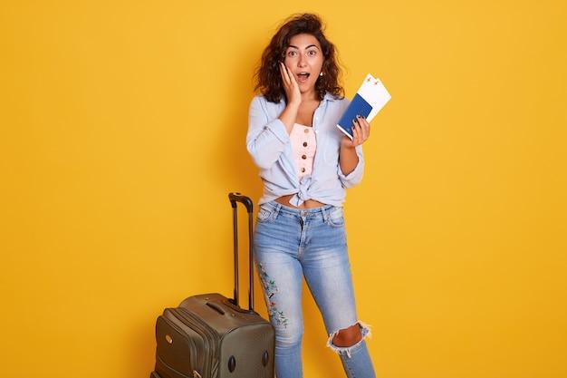 彼女の灰色のスーツケースの近くに立ってカジュアルな服を着て旅行者観光客女性 Premium写真