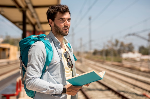 Traveler waiting for train on station platform Free Photo