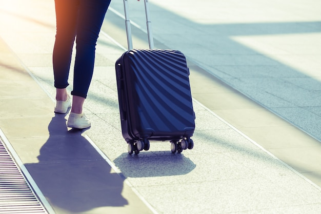 Traveler walk on street with suitcase with sunset light travel concept Premium Photo