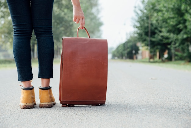 Traveler with vintage backpack on the road Free Photo