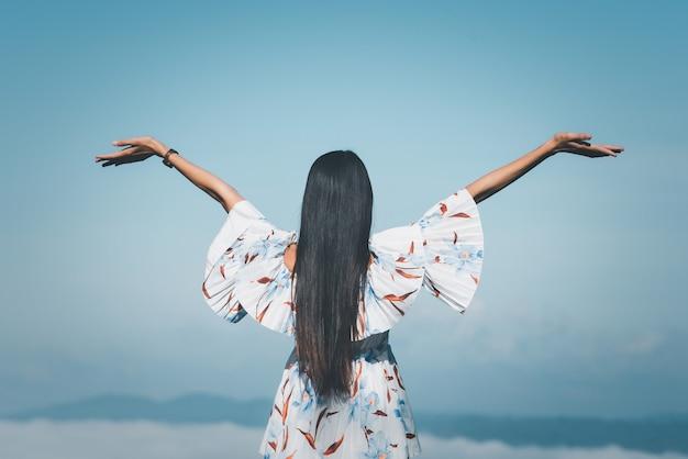 일출 산에서 안개를 찾고 제기 손으로 서 여행자 여자. 프리미엄 사진