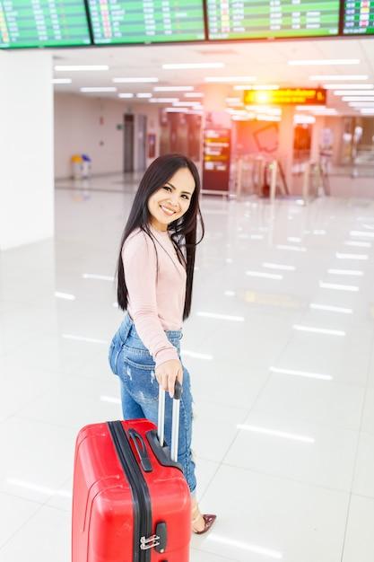 Traveler woman walking carrying a suitcase in international airport Premium Photo