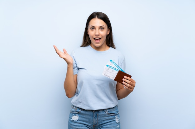 Traveler woman with boarding pass over isolated blue wall with shocked facial expression Premium Photo