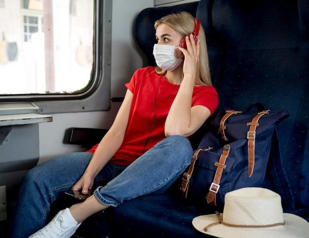 Donna del viaggiatore con musica d'ascolto della maschera Foto Gratuite