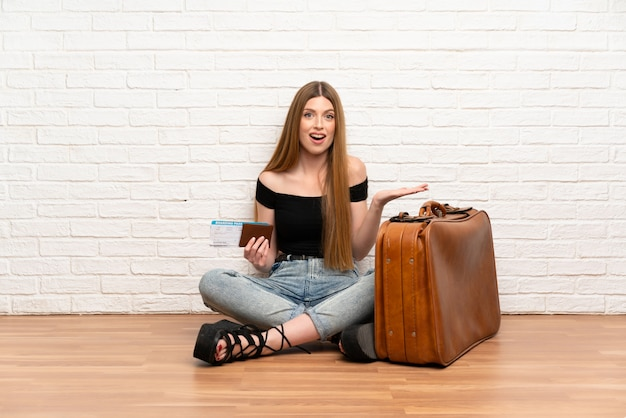 Traveler woman with suitcase and boarding pass with shocked facial expression Premium Photo