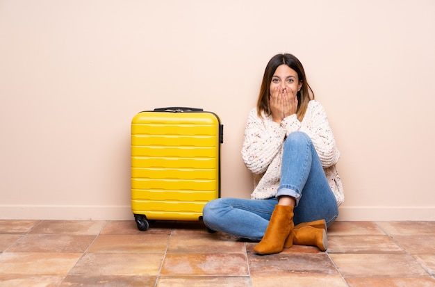 Traveler woman with suitcase sitting on
