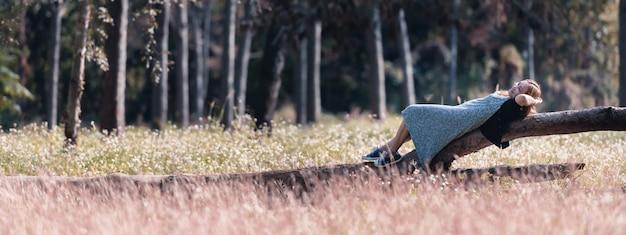 Путешественник молодая азиатская женщина лежа на журналах в парке на каникулах Premium Фотографии