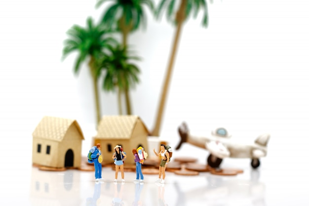 Travelers standing with houses and planes on coins. Premium Photo