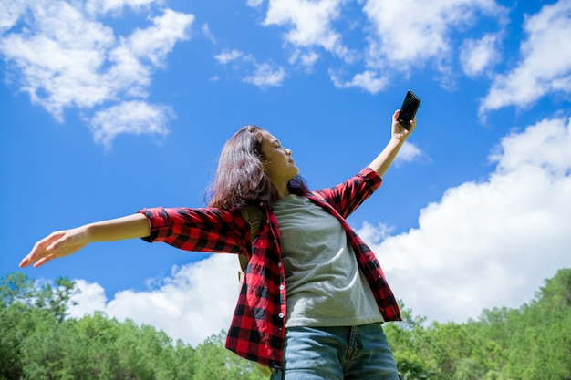 旅行者、若い女性は、素晴らしい山と森、放浪癖のある旅行のアイデア、メッセージのためのスペース、素晴らしい雰囲気の瞬間を見ます。 無料写真