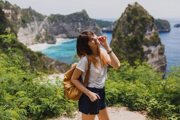 旅行と冒険のコンセプトです。ヌサペニダ島のインドネシア旅行バックパックで幸せな女。 無料写真