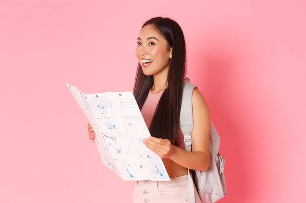旅行、ライフスタイル、観光の概念。魅力的なアジアの女の子の観光、地図を見てバックパックを持つ旅行者の側面図、都市を探索、観光やホステルの検索、ピンクの壁 Premium写真