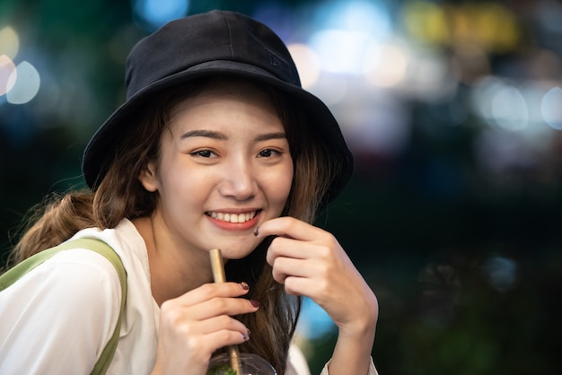 Traveling lifestyle of asian girl with drinking water glass at nigh Premium Photo