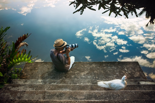 Traveling man taking a photograph at old pier against beautiful blue sky reflection on water floor Premium Photo