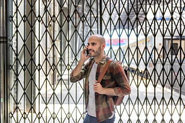 Traveling man talking over phone Free Photo