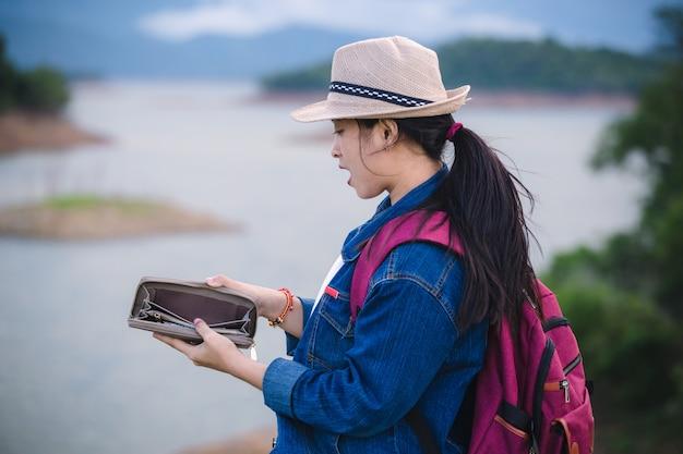 Traveling people concept. portrait of asian girl open empty wallet Premium Photo