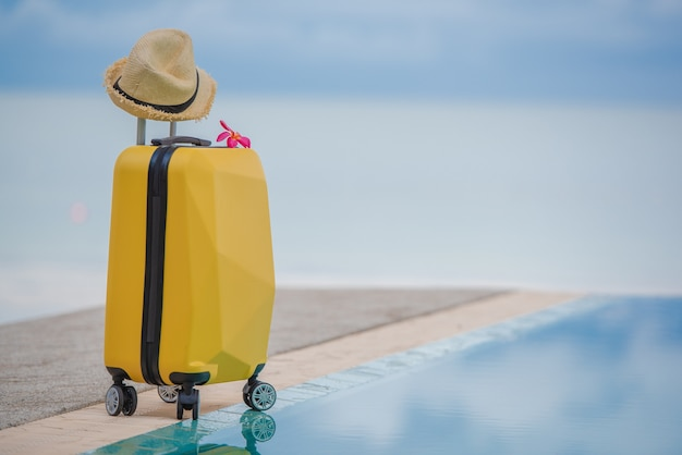 Traveling suitcase and hat on beautiful seascape with reflection Premium Photo