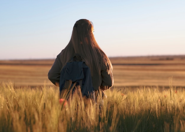 Traveling woman with backpack. is in the field watching sunset, barley wheat field Premium Photo
