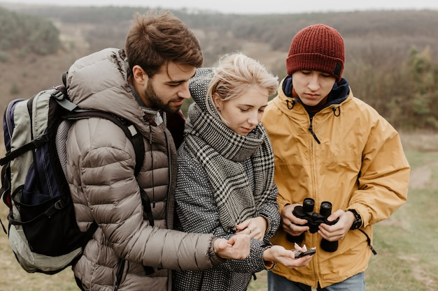 Traveller friends looking at compass Free Photo