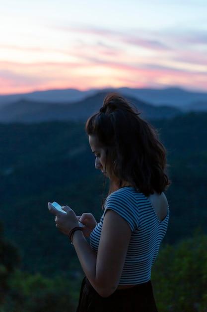 Viaggiatore guardando il suo telefono con le montagne sullo sfondo Foto Gratuite
