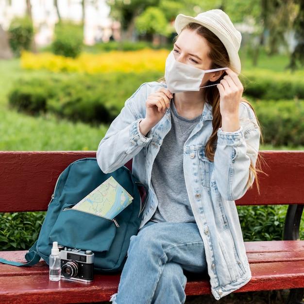 医療用マスクを着用し、座っている旅行者 無料写真