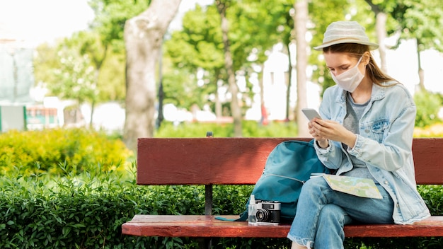 Traveller wearing medical mask in the park Free Photo