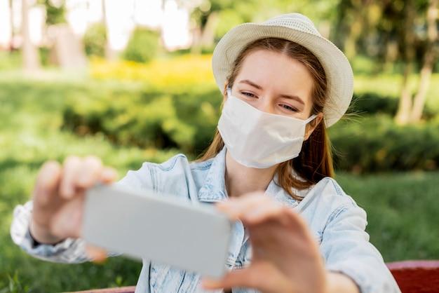 Путешественник в медицинской маске, делающий фотографию Бесплатные Фотографии