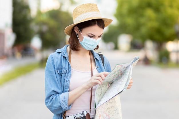 マップをチェックする帽子とフェイスマスクを持つ旅行者 無料写真
