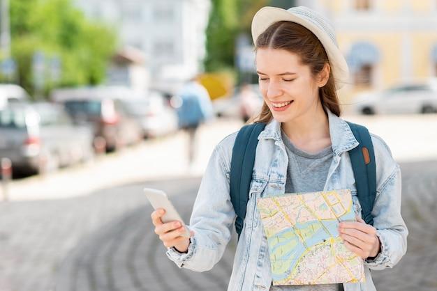 Viaggiatore con la mappa e il cellulare di medio livello Foto Gratuite